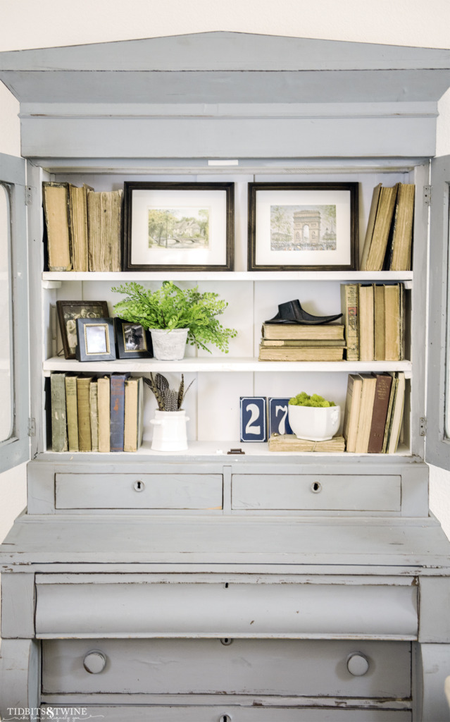 Blue gustavian hutch with antique books, art and organic items