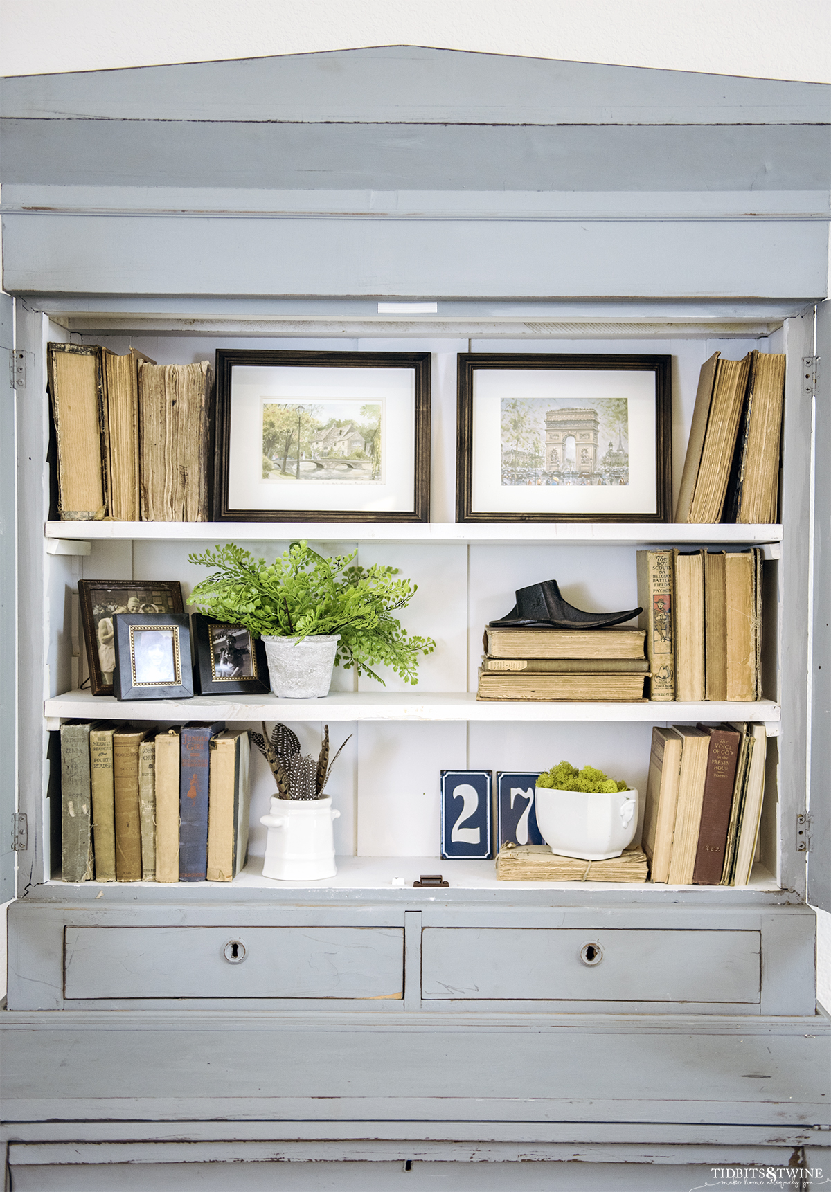 french blue cabinet styled with antique books and white ironstone and two pieces of art on the top shelf