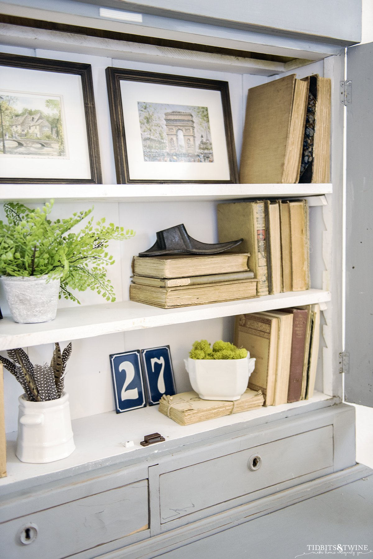 An antique blue French cabinet styled with books and art
