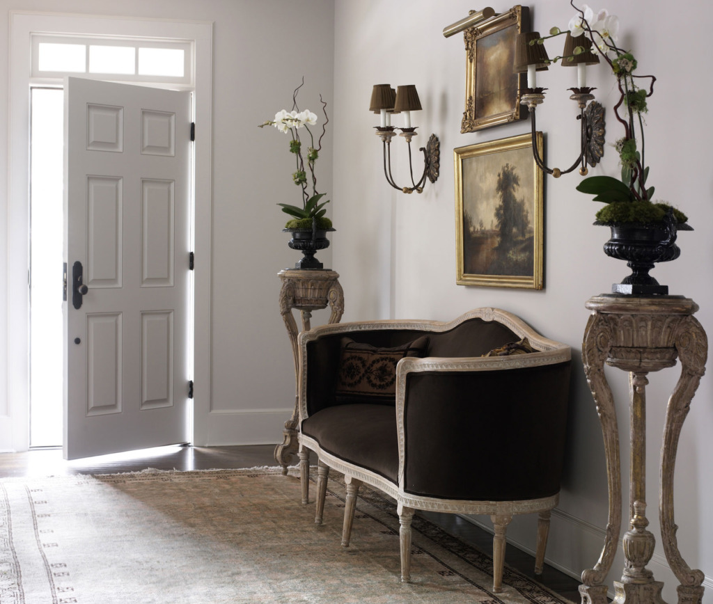elegant foyer with french velvet settee flanked by orchids on stands