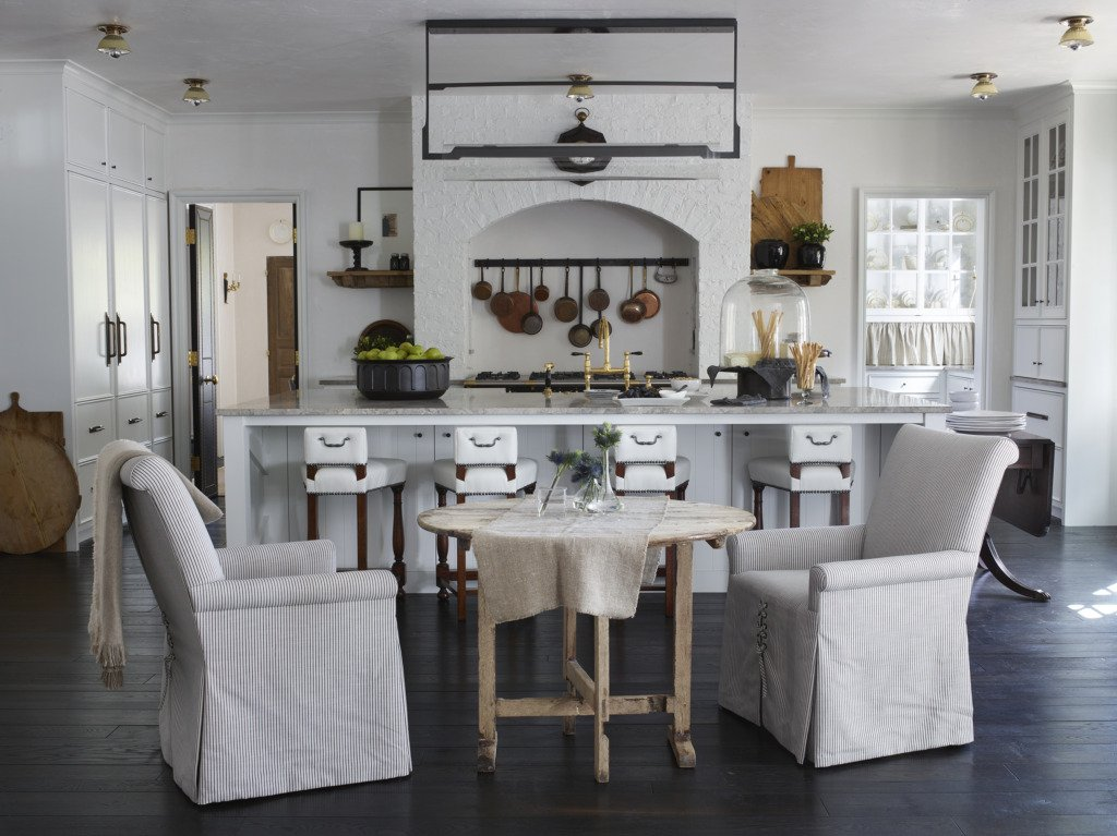 White kitchen with brick range french antiques and wine table sitting area