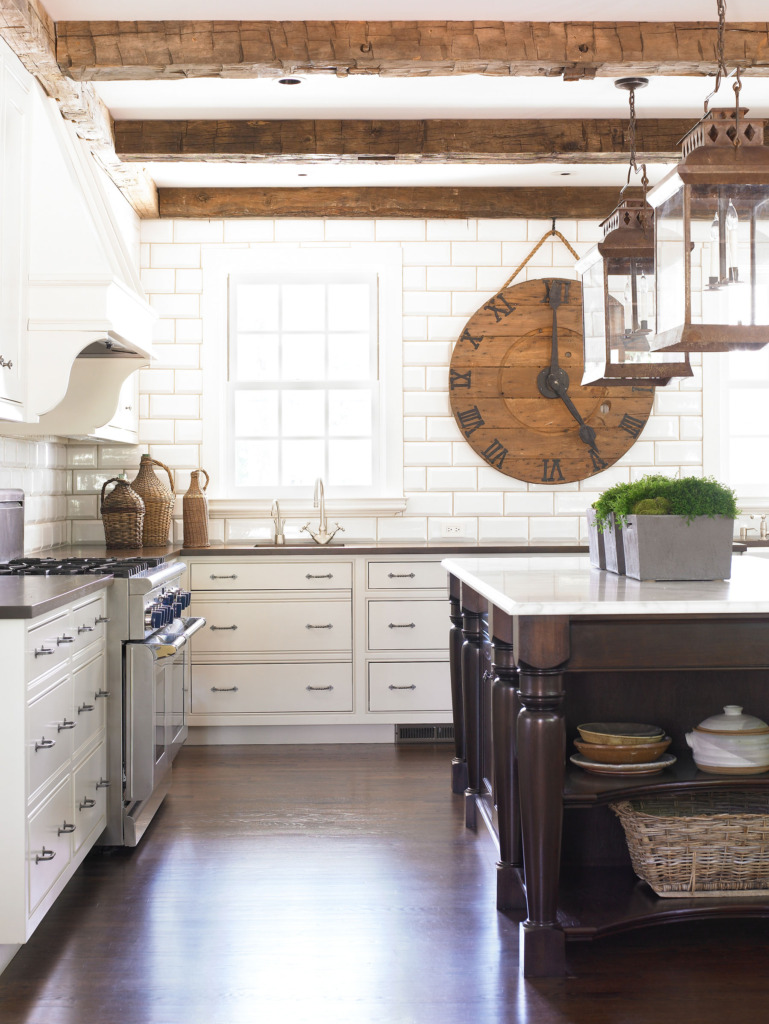 White kitchen with subway tile and dark wood island with antiques