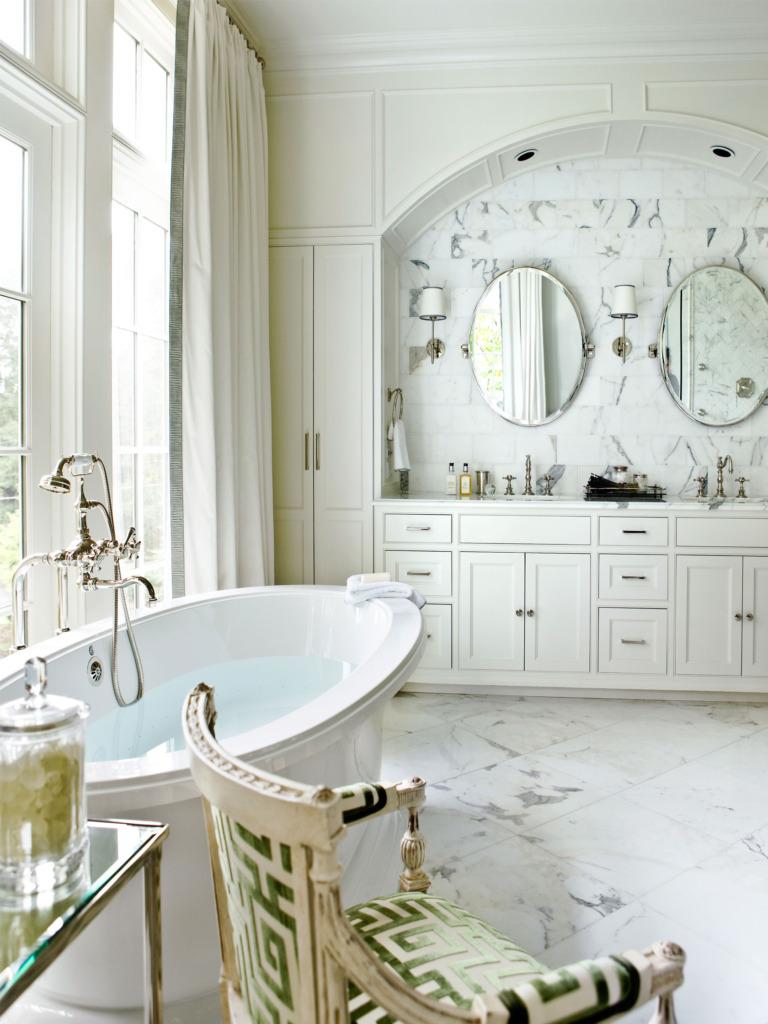 marble master bathroom with freestanding tub overlooking window