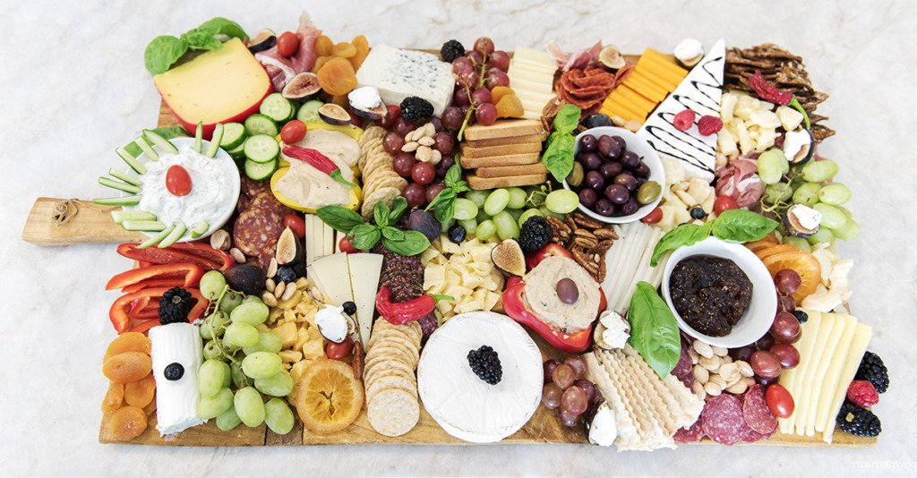 DIY delicious oversized charcuterie board with meats cheeses nuts fruits and vegetables