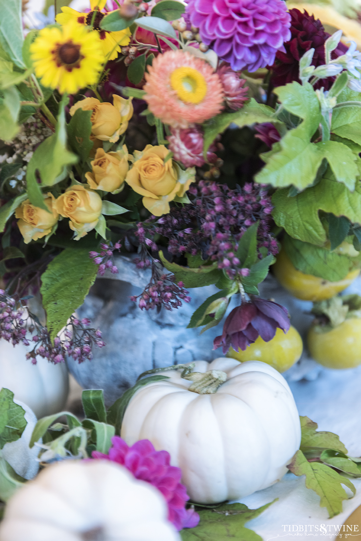 closeup of small white pumpkins on dining table surrounded by fall floral display in pinks greens and orange