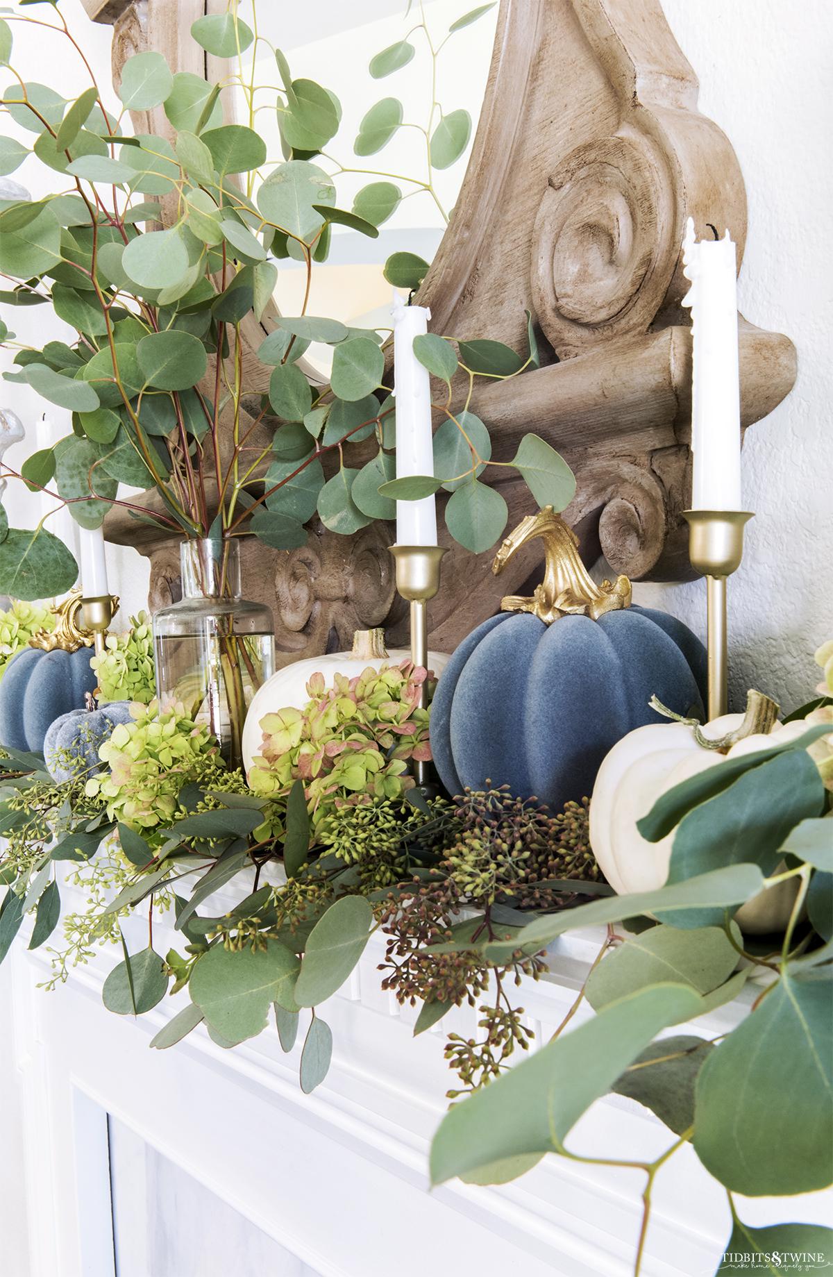 Closeup of blue velvet pumpkin gold candlesticks and eucalyptus on mantel