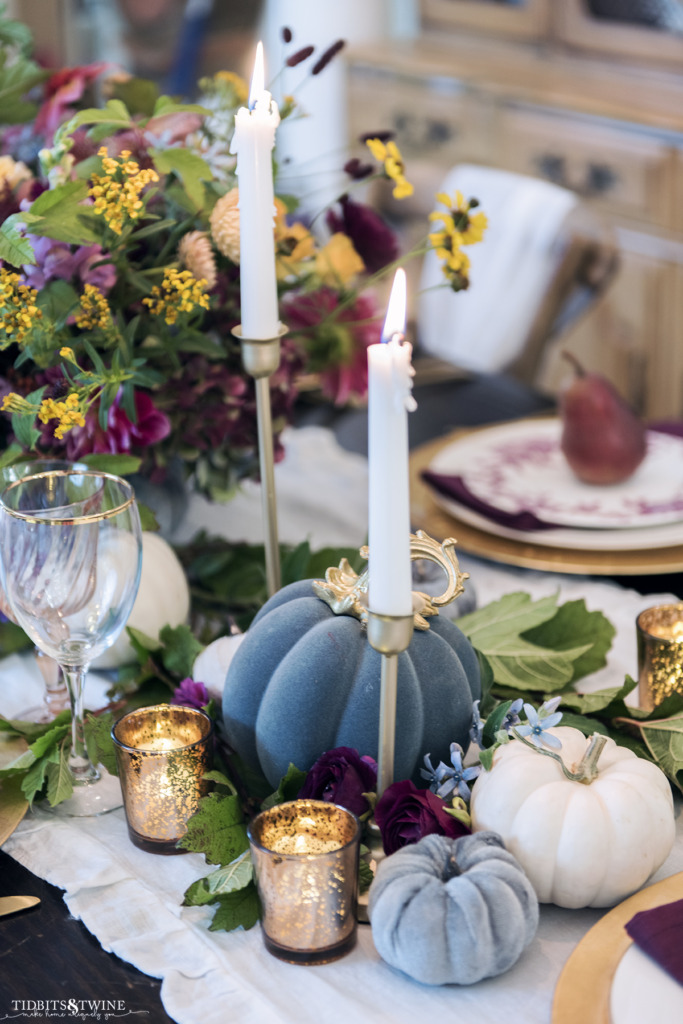 Fall dining table with dripping white candles in a gold taper with blue and white pumpkins
