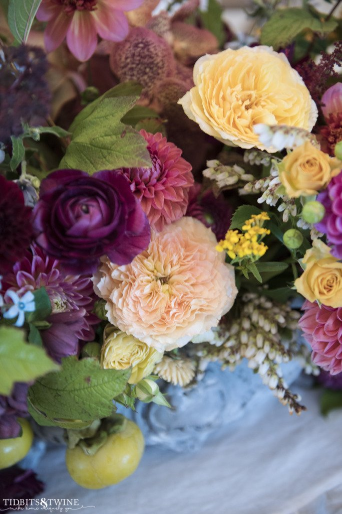 closeup of pink dahlias and yellow roses in blue antique french jardinere