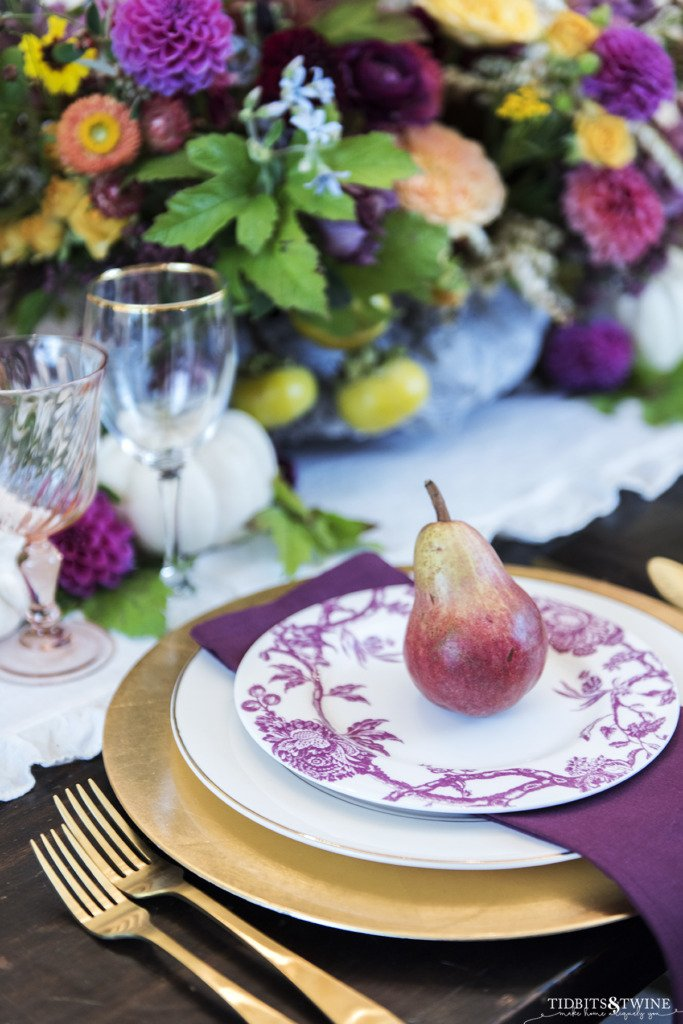 close up of fall table setting in burgandy with red pear on the plate and purple floral centerpiece