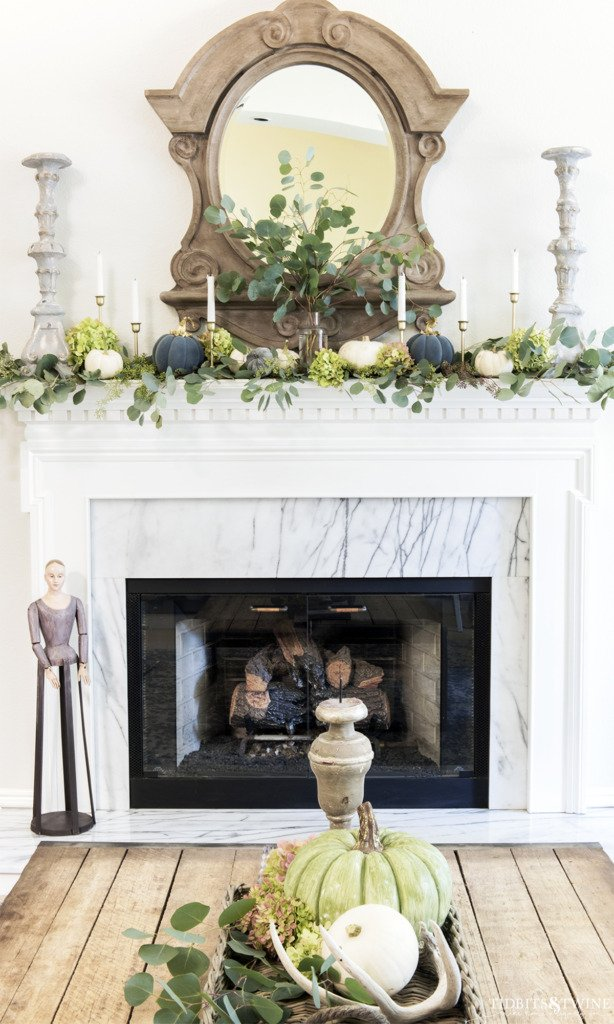 Living room fireplace decorated for fall with mansard mirror above and eucalyptus on mantel