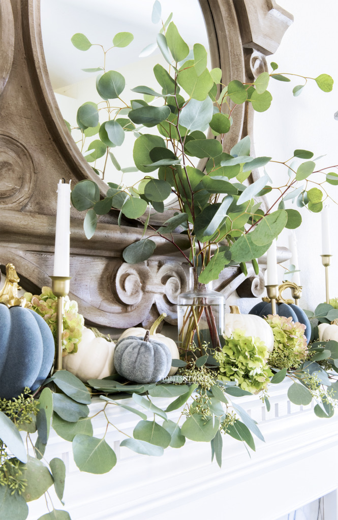 Fireplace mantel decorated for Fall with eucalyptus branches in a glass vase with little pumpkins around