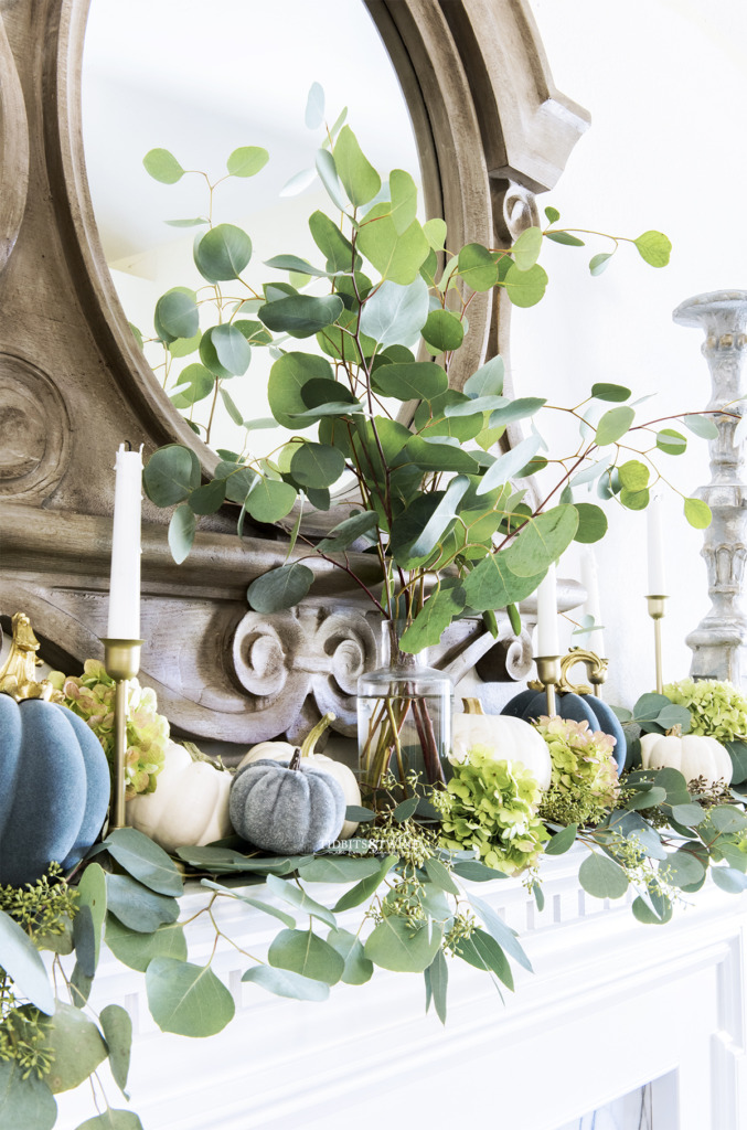 Eucalyptus branches in a vase with little pumpkins and candlesticks on a Fall french mantel