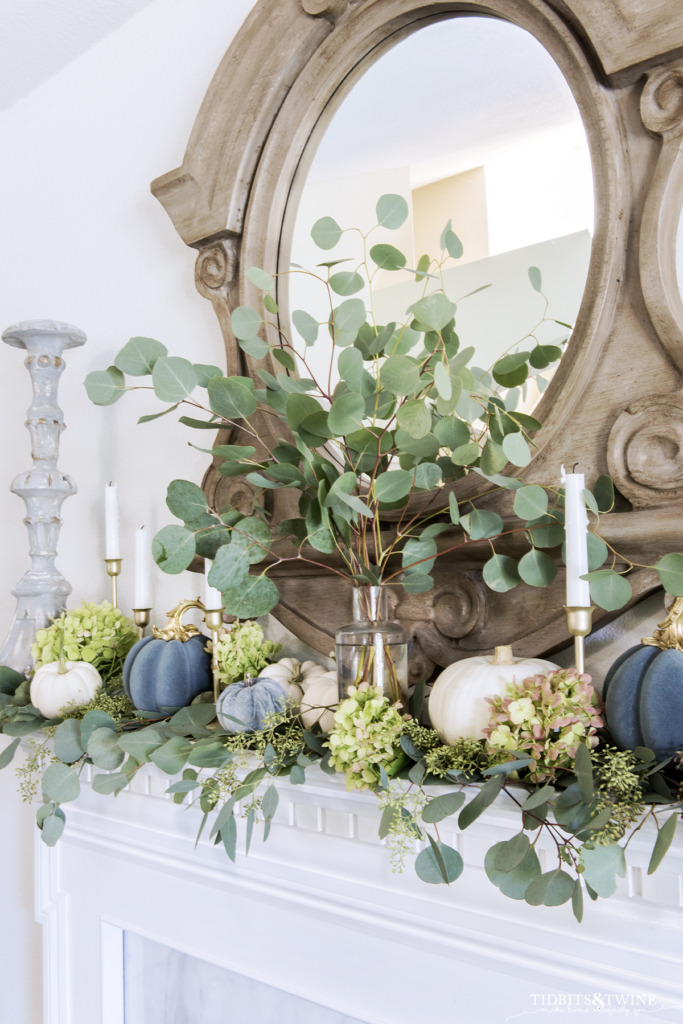 Fall french mantel decorated with eucalyptis white and blue pumpkins and candlesticks
