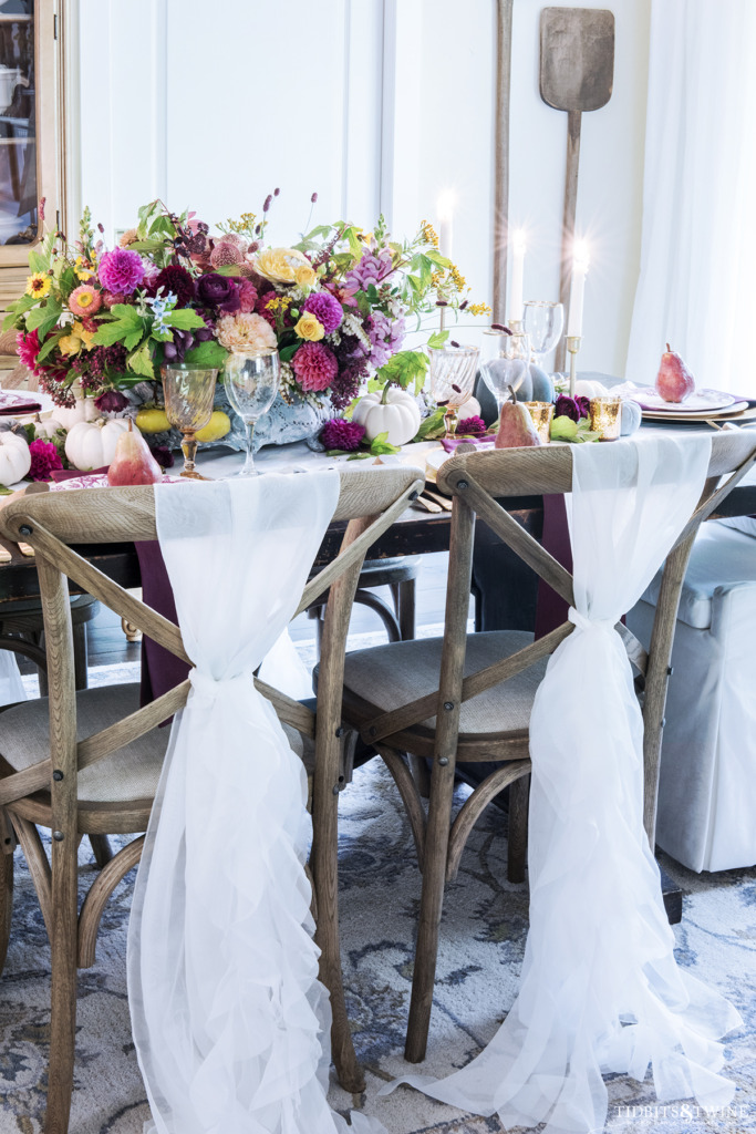 fall french dining room with white chairs and oversized colorful flowers and pumpkins on the table