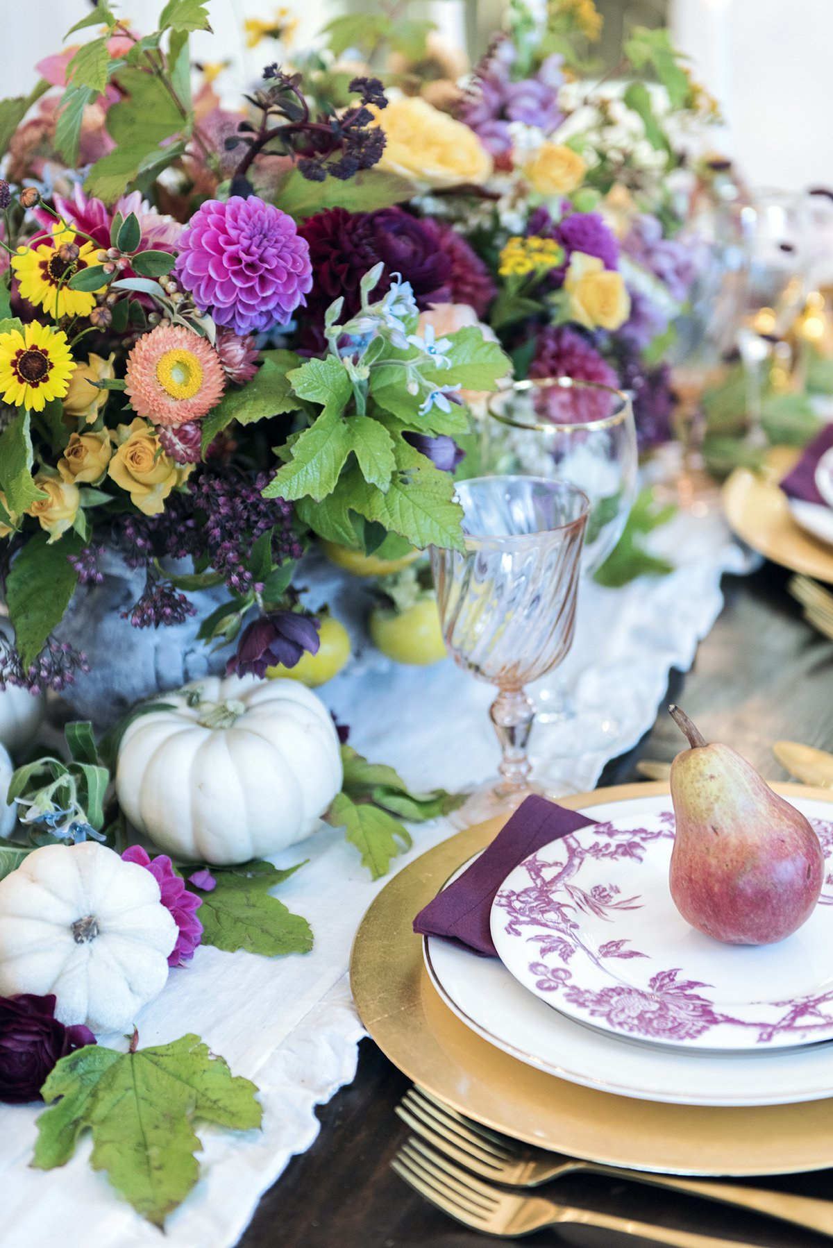 gold and purple fall french place setting with large flower centerpiece and pear on top of plate