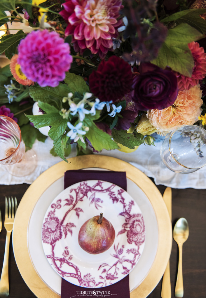 top down shot of fall place setting with burgandy plate and gold charge with pear on top