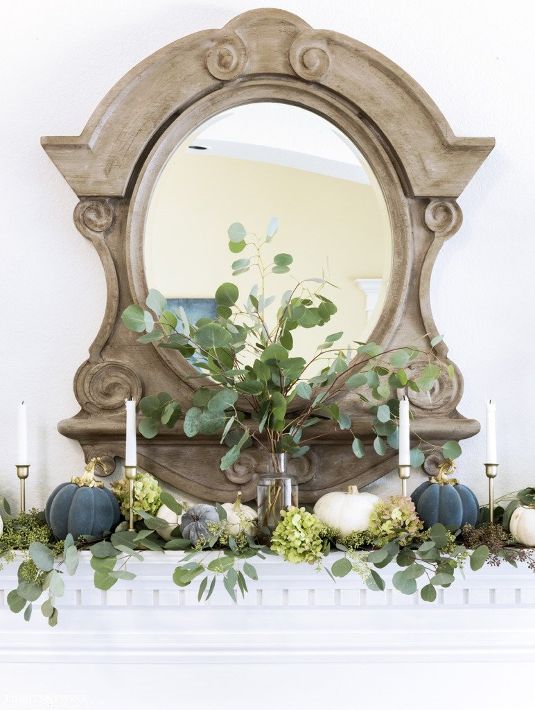 Clear vase on mantel holding eucalyptus with french mirror above