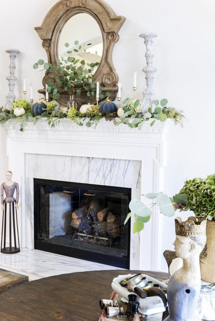 White French mantel with carrera surround decorated for Fall with eucalyptus and white pumpkins
