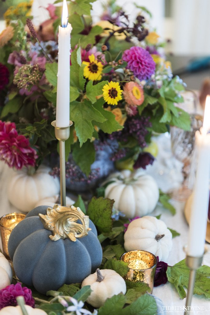 blue velvet pumpkin with gold stem with white candles in gold candlesticks and fall flowers