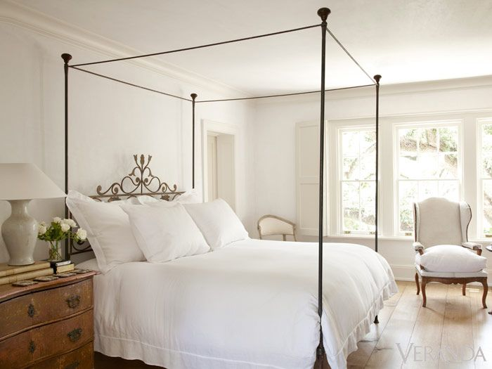 White master bedroom with french iron four poster bed and white linens