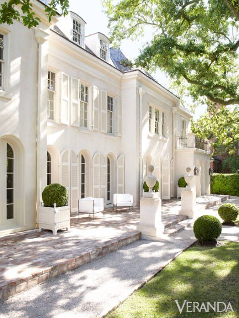 Two store white chateau with arched windows and french planter boxes