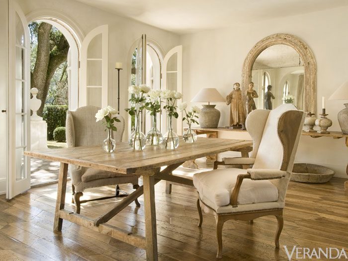 Neautral French dining room with wooden floors and two wingback chairs at table