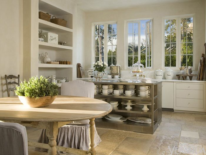 White kitchen with open shelving and round french table with slipcovered chairs