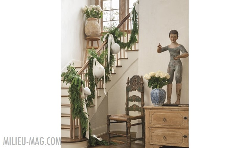 Plaster and wood stairs with cedar garland and white ornaments