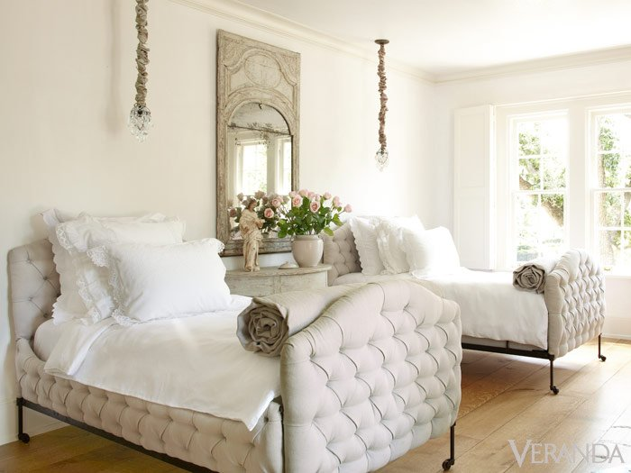 White bedroom with two twin white tufted beds and french mirror between