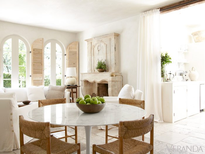 French eating area with round table and rattan chairs on travertine floor and fireplace