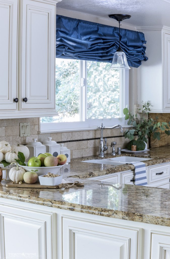 french kitchen with partial overlay cabinet doors and blue curtain above window
