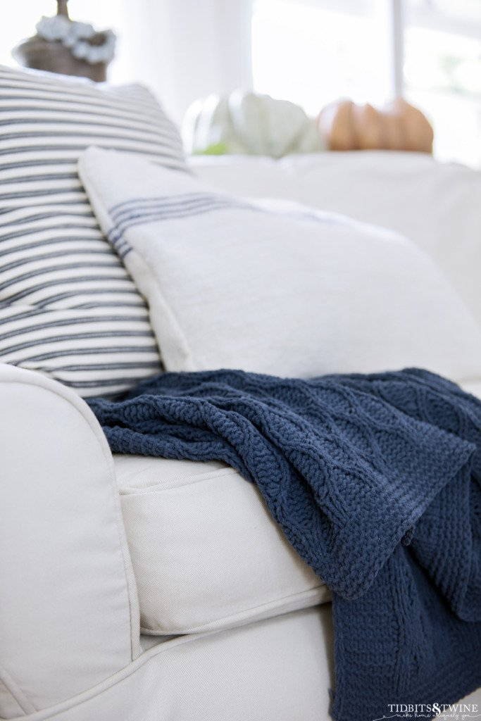 White slipcovered sofa with blue cableknit throw in Fall family room
