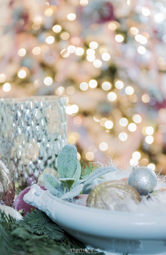Closeup of ironstone tureen filled with pink Christmas ornaments and tree in background
