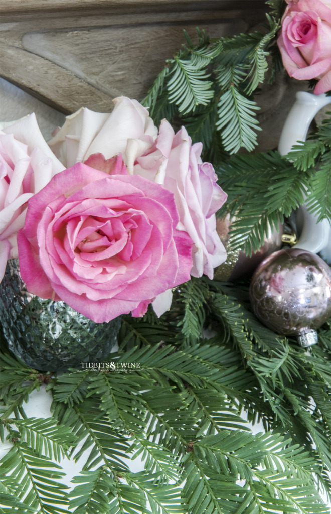 Pink rose in mercury vase with greenery and ornament on fireplace mantel