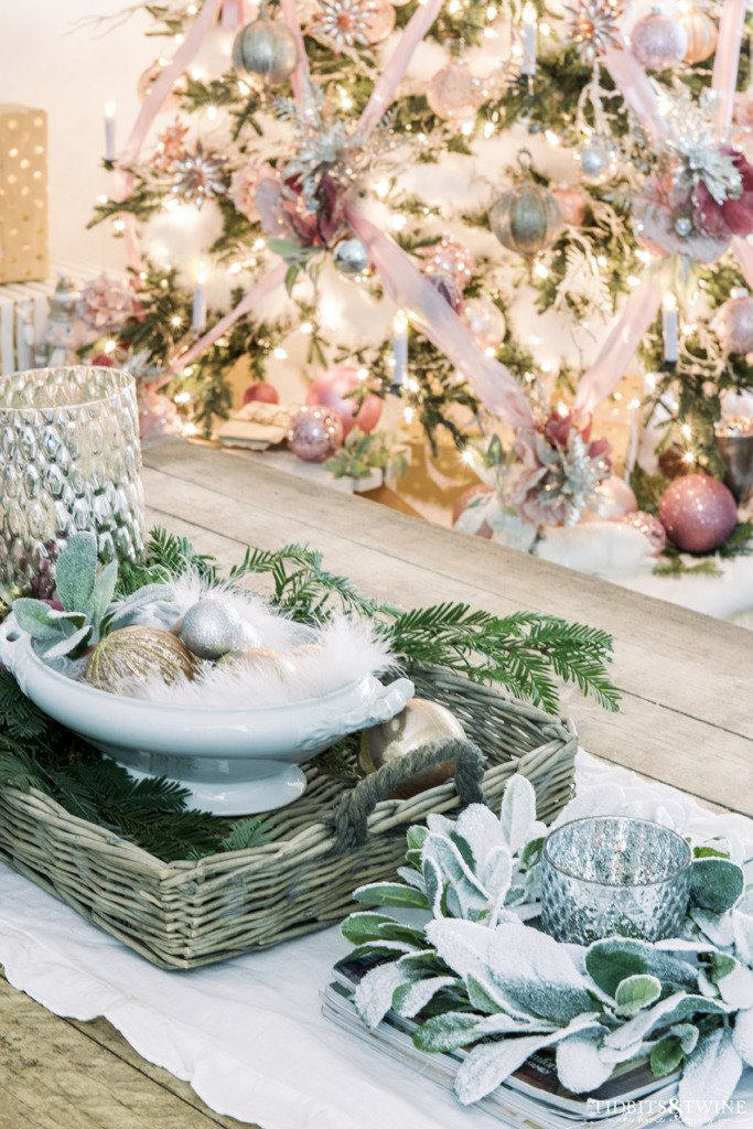 Industrial coffee table decorated for Christmas with pink ornaments and greenery