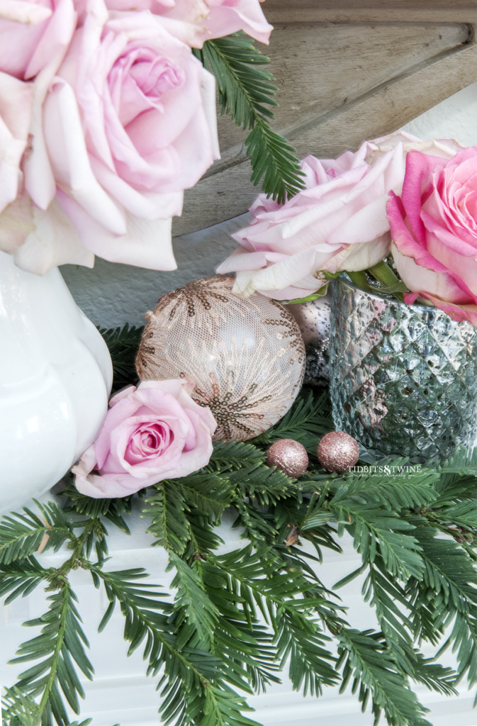 Pink Christmas ornaments with roses and greenery on a fireplace mantel