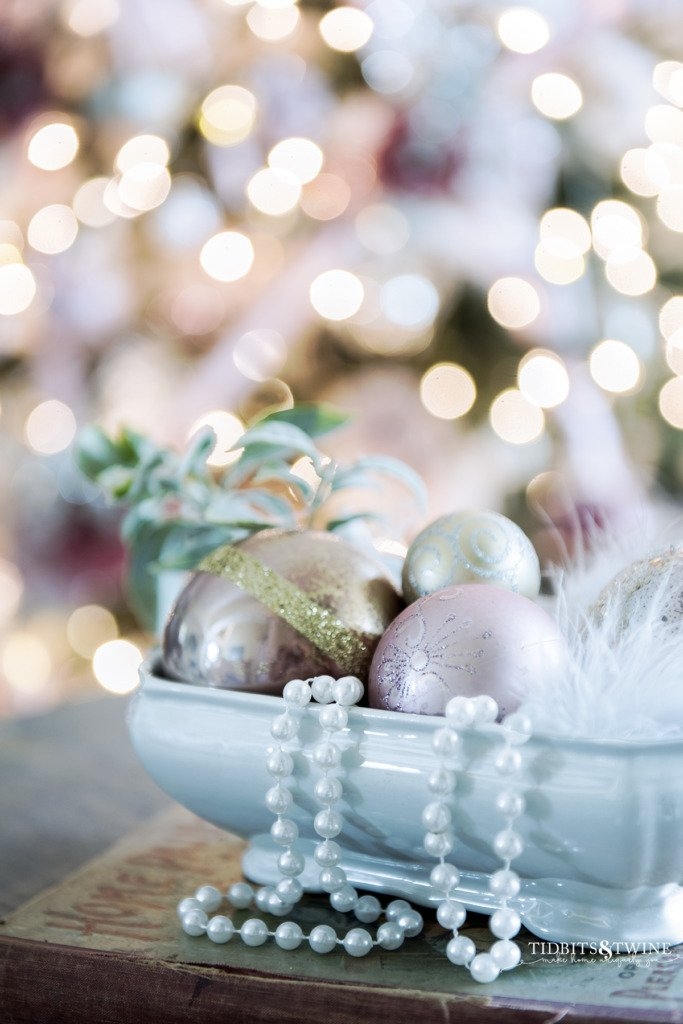 Closeup of white ironstone filled with pink Christmas ornaments and tree in background