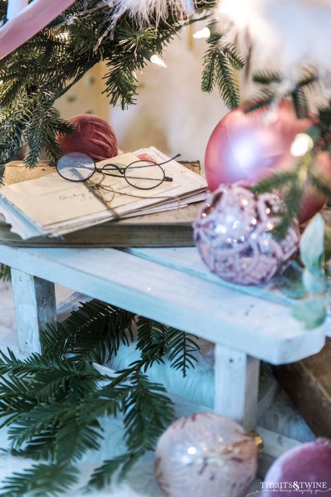 Wood sled underneath a Christmas tree with pink ornaments and vintage books