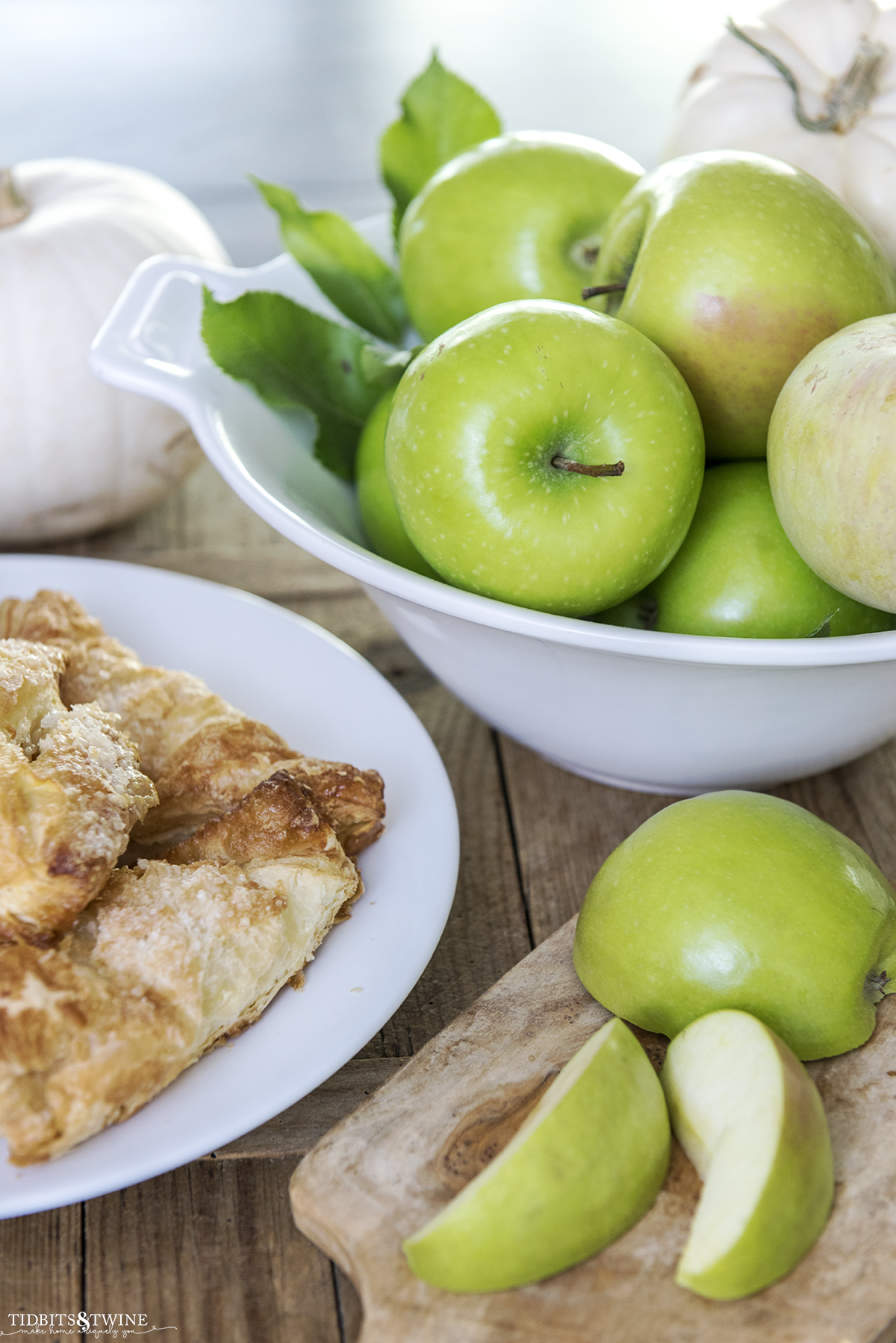 White bowl of green apples with apple turnover on a plate for Fall