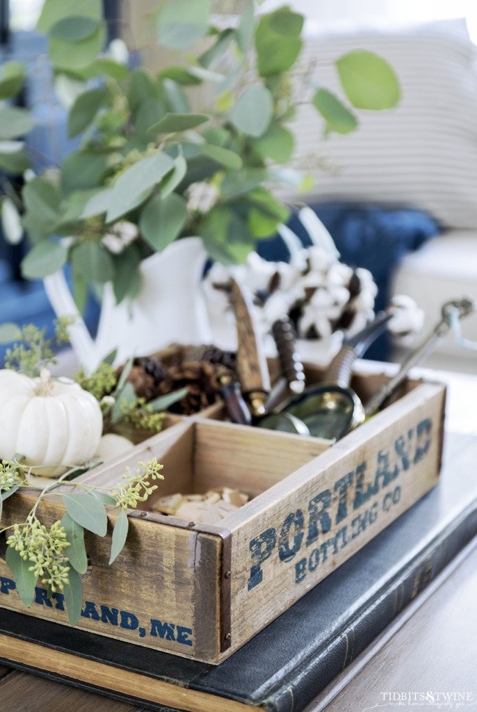 Wooden bottle crate with pumpkins pinecons and magnifying glass collection on fall table
