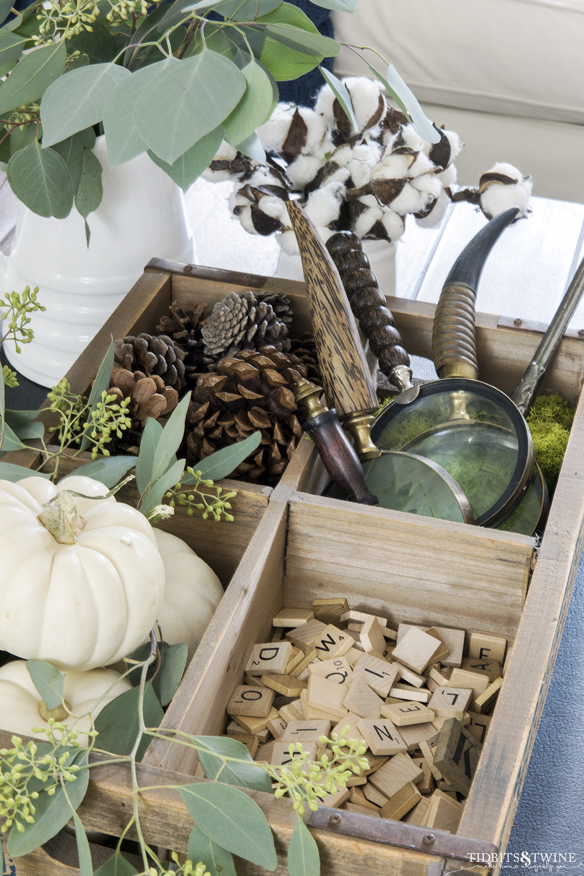 Wooden tray with compartments holding Fall items like pumpkins, pinecones and wooden scrabble tiles