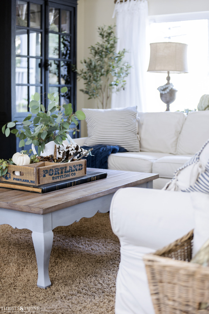 French coffee table with fall decor on top in family room with white pottery barn sectional sofa