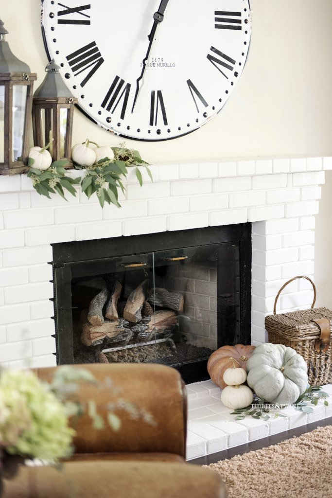 white brick fireplace mantel with large french clock above decorated for fall with pumpkins and eucalyptus