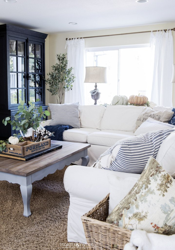 french family room decorated for fall with pumpkins and eucalyptus and touches of blue