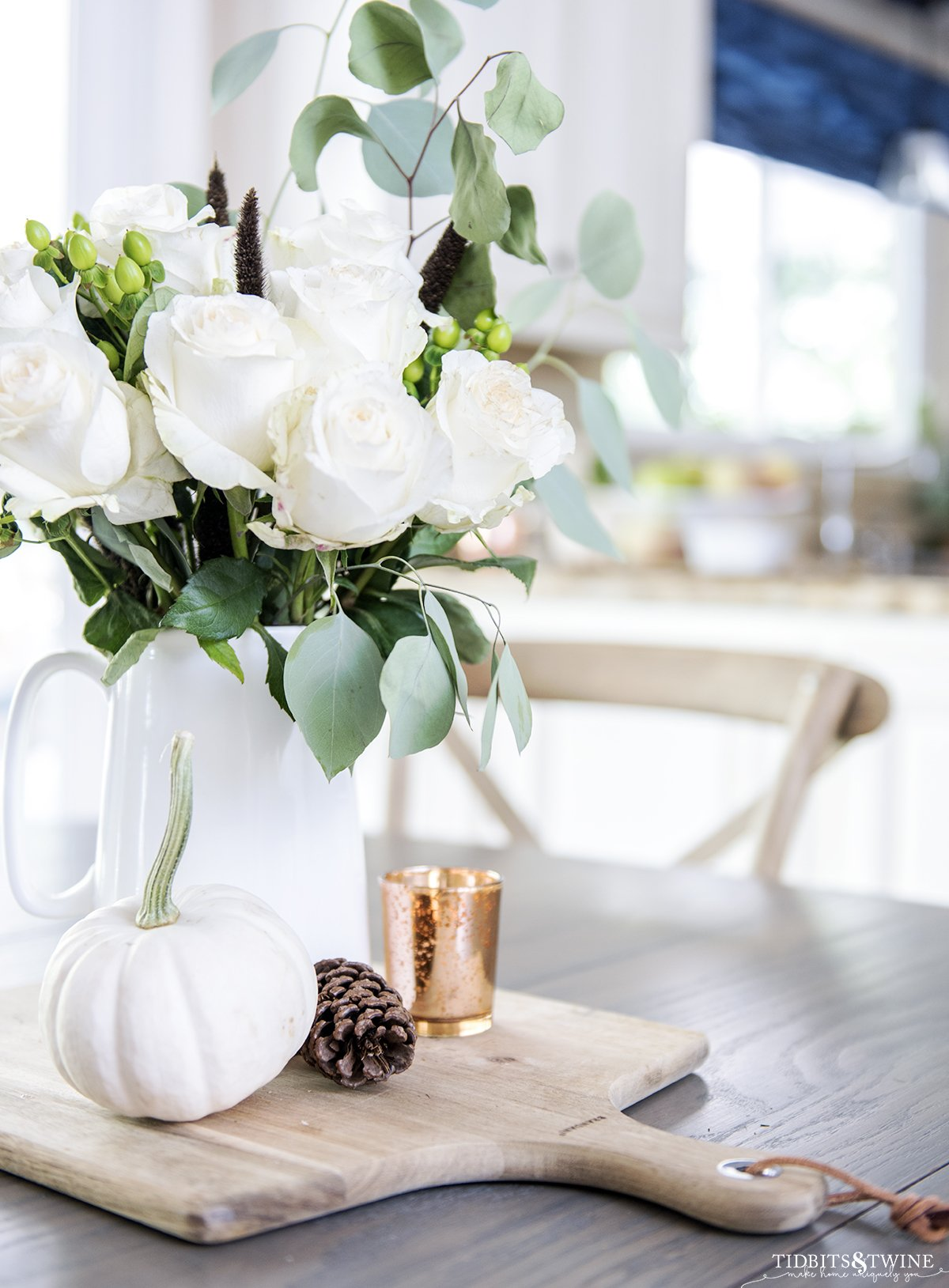 White roses in a white pitcher sit on a French country table in a kitchen more decorating tips here