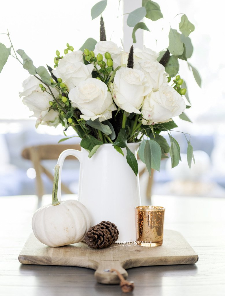 Table centerpiece for Fall with white pitcher holding white roses on a bread board with pinecone and pumpkin