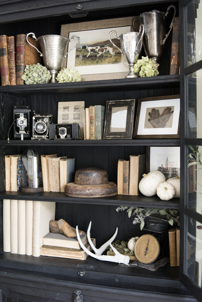 black french cabinet decorated for fall with antique books tropies and dried hydrangea