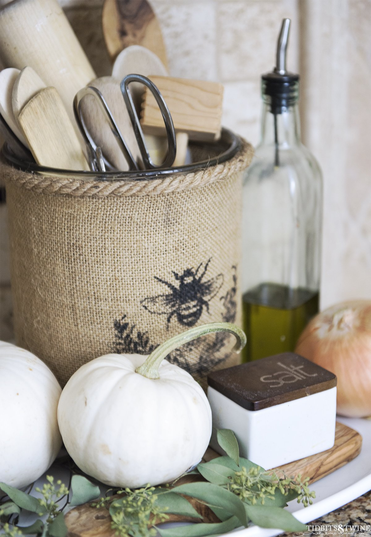 Burlap vase kitchen utensil holder with white pumpkins decorated for Fall