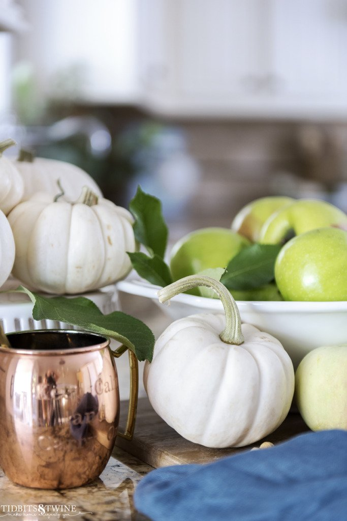 Fall vignette with white pumpkins and green apples with a copper mule mug