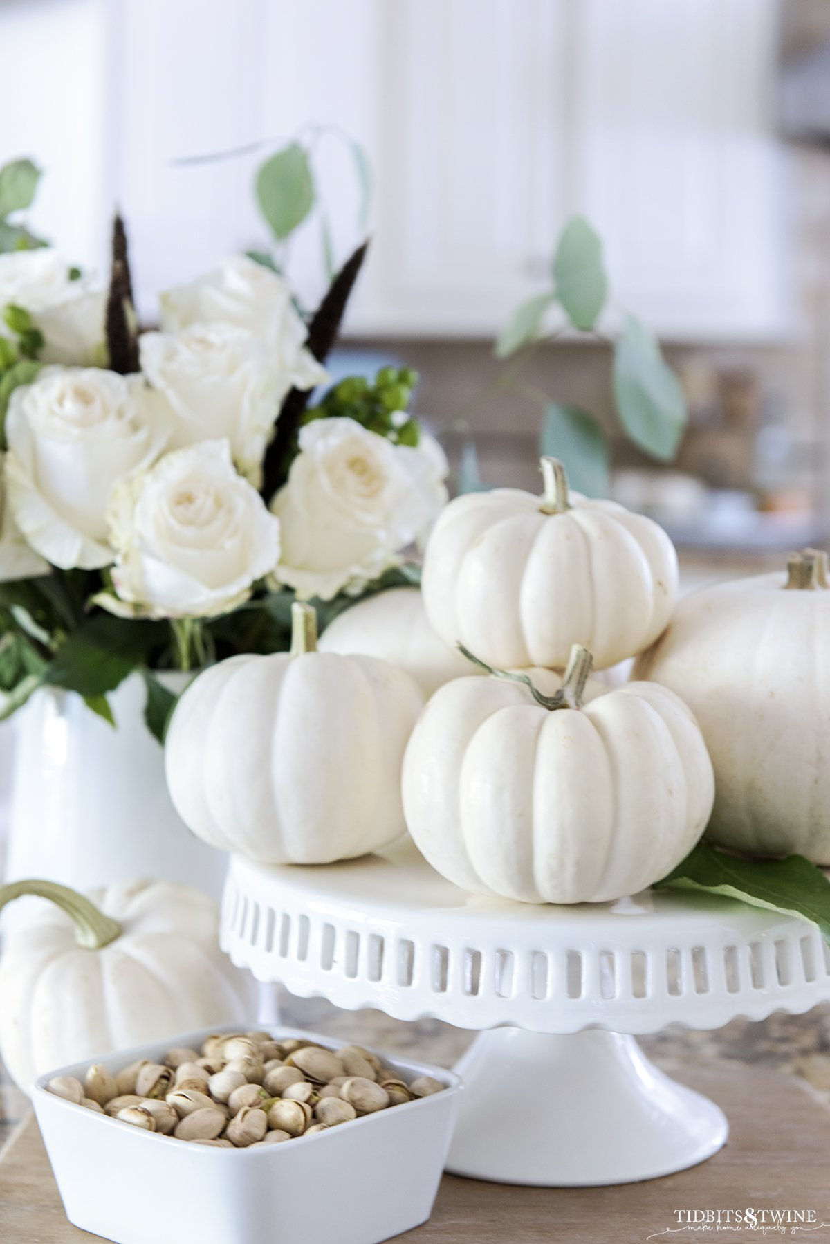 Small white pumpkins on a cake stand with a pitcher of white roses behind and a bowl of pistachios below